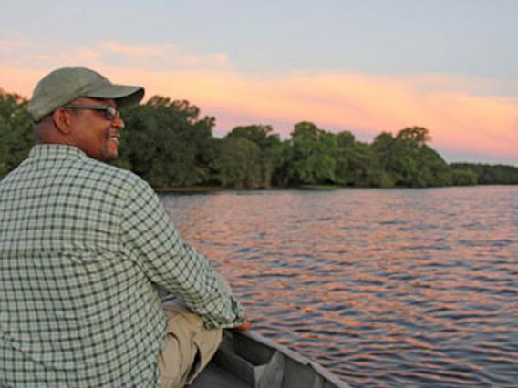Stuart on a boat on the water during sunset